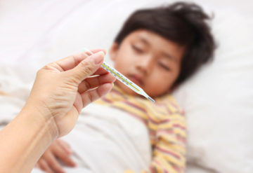 Small child with fever has his temperature checked