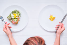 Choosing between two plates: on the left, salmon and on the right, supplements.