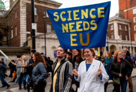 "A scientist protesting Brexit holds a ""Science needs EU"" banner on a march in London"