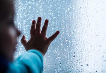 Close-up of child's hand on wet window
