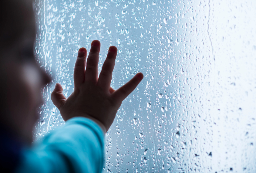 Close-up of child's hand on wet window