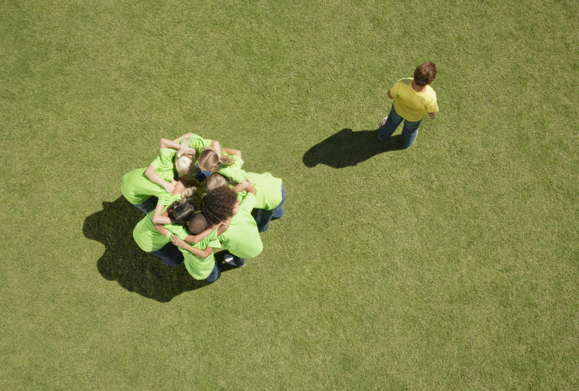 boy alone outside of group on playing field
