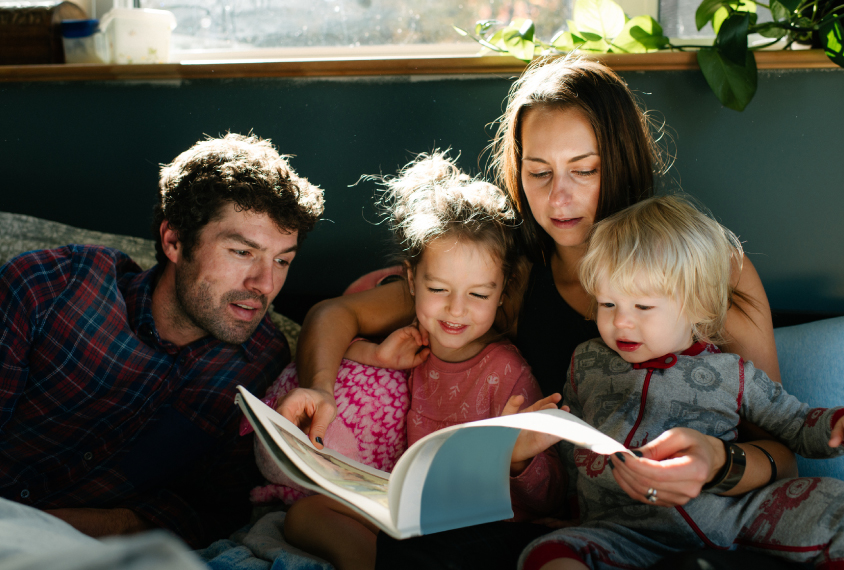 Young family of four reading together