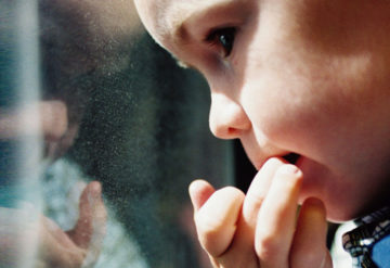 Young boy biting his fingernails, looking anxiously out the window.