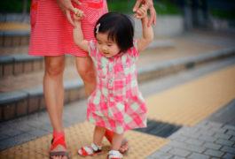 幼儿在妈妈的帮助下保持平衡