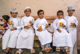 Young boys in Oman in a market sit and drink juice