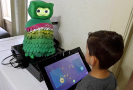 Young boy is interacting with a small rubbery green colored robot through a touch screen.