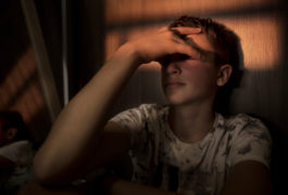 Teenage boy sitting alone, hand over his eyes, in the fading light.