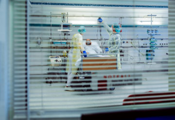 patient in hospital on ventilator, seen through a window.