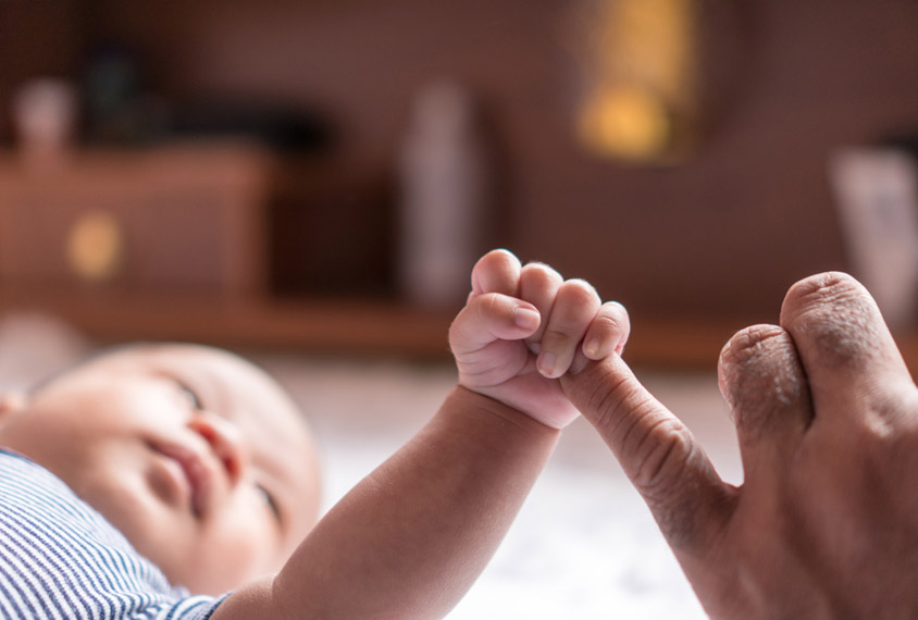 baby grasping an adult hand