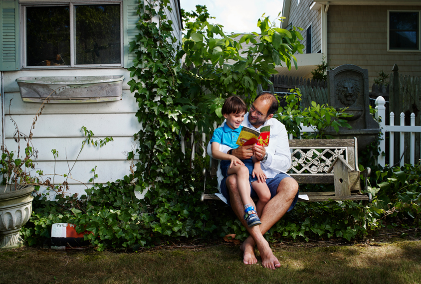 Matt Lerner reading to his son in the backyard of his house.