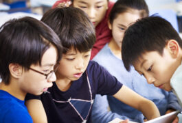 一小群中国学生一起看平板电脑。