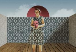 从图片上看,一名女子拿着一个面具,她的裙子与身后的墙纸相配。