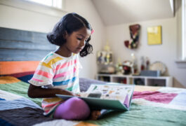 Young child on her bed looking at a book.