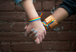 Close-up of two hands holding and wearing rainbow-striped bracelets.