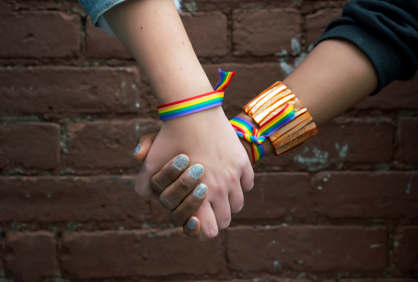 特写的两只手握着并戴着彩虹条纹的手镯。