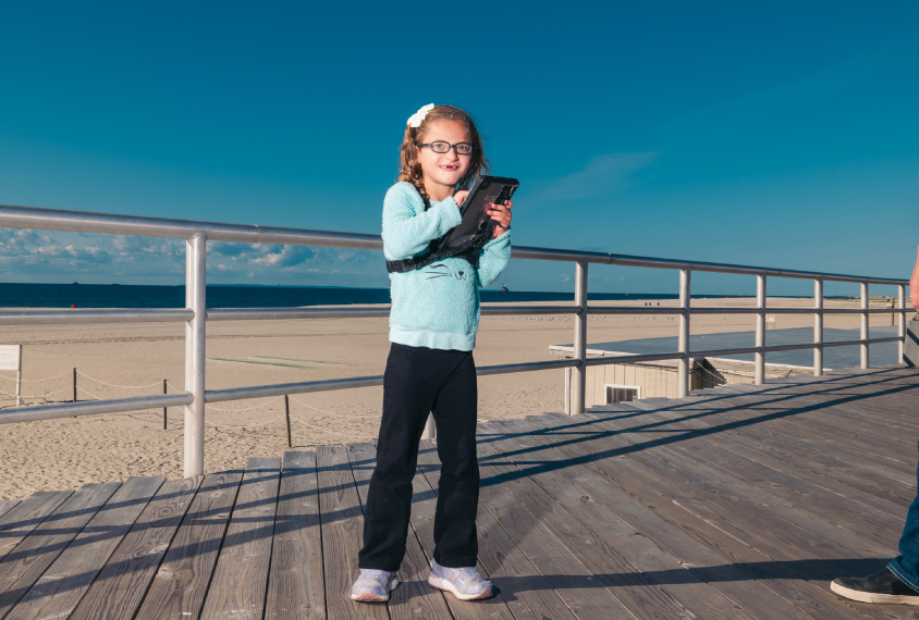 Qunicy holds her ipad on the boardwalk at Atlantic Beach, NY. The ipad has been programmed so that she can select words on the touchscreen and the ipad will then speak that word. At this moment Quincy has just chosen the word 'playground.'