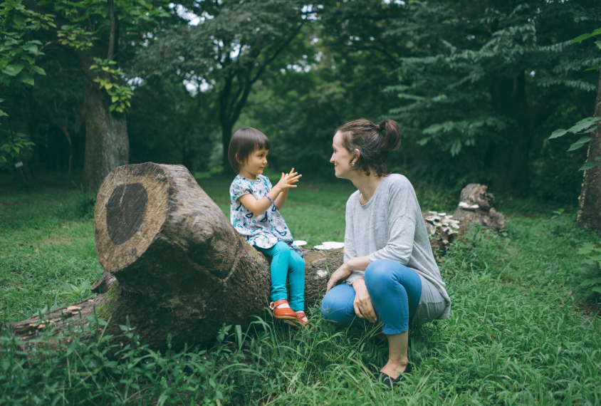 Mother and child having a conversation in nature.