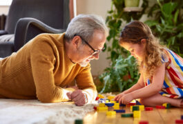 Mature dad and his daughter plays with blocks