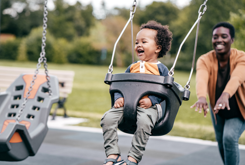 Black mother pushing her child on swing at playground.