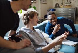 一个微笑的小男孩在家里学习的时候,在沙发上向朋友展示手机