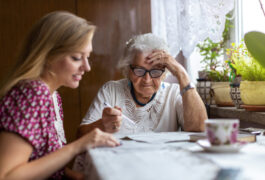 Photograph shows young woman and older woman discussing paperwork.