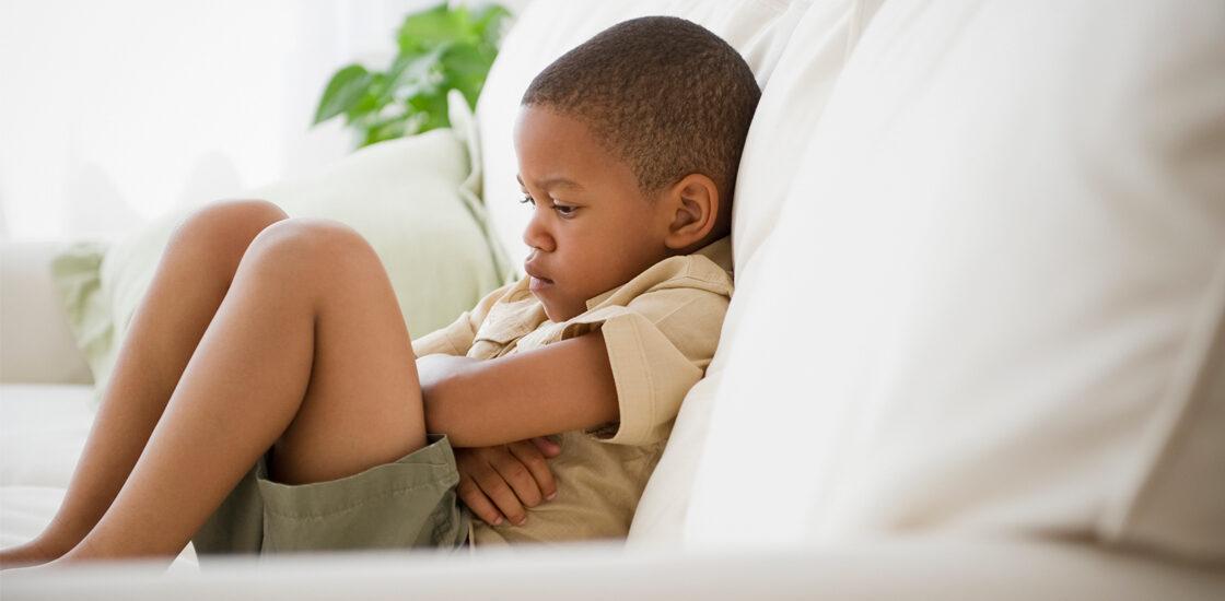小男孩看起来很沮丧,双臂交叉坐在沙发上。