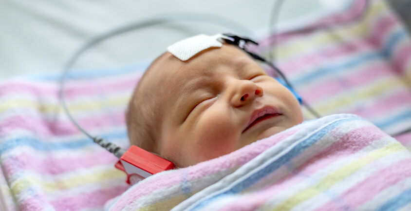 Infant in hospital blankets undergoes a hearing test.