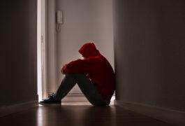 Depressed teenager sitting on floor in darkened hallway.