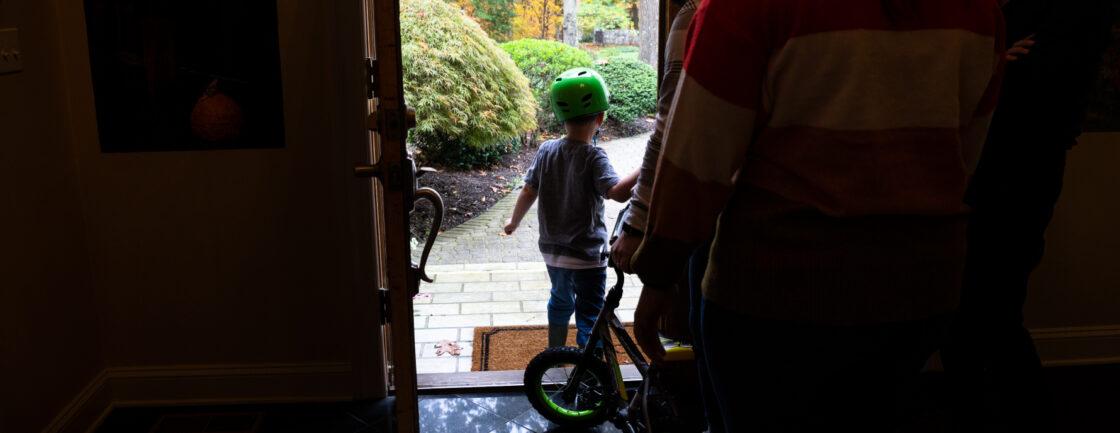 欧文离开家去骑自行车,后面跟着他的治疗师和老师。