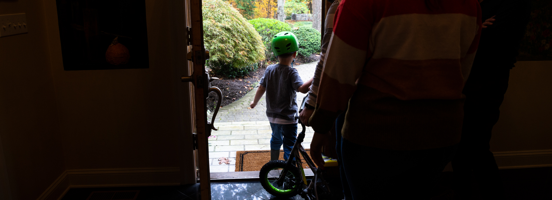 Owen leaving his home for a bike ride, followed by his therapists and teachers.