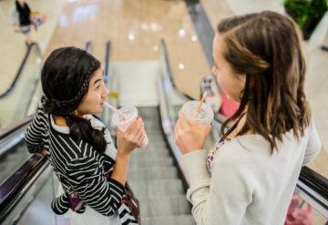 两个十几岁的女孩在自动扶梯上聊天。