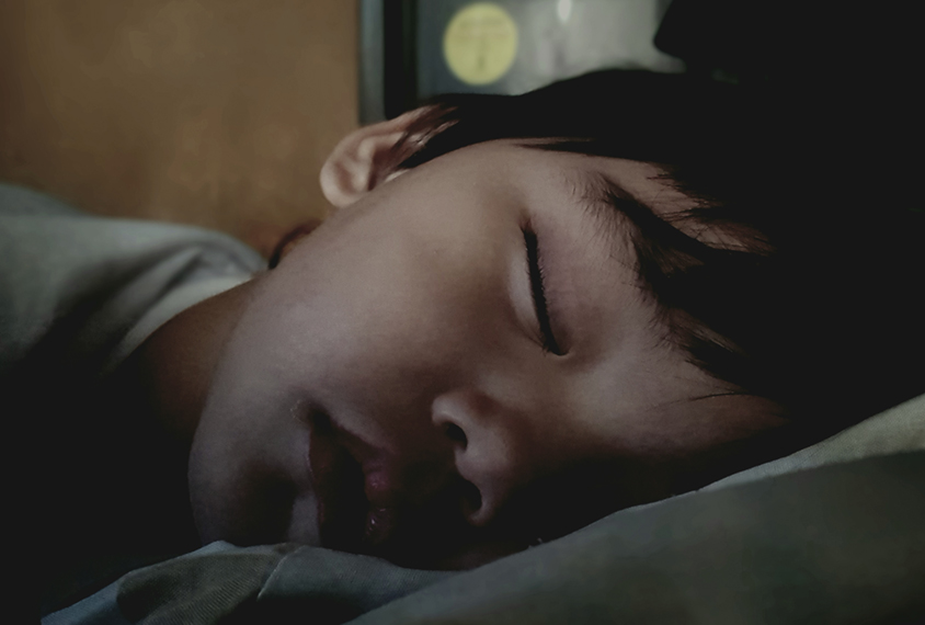 小男孩在昏暗的灯光下睡觉