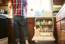 年轻人在厨房水槽旁打开洗碗机。