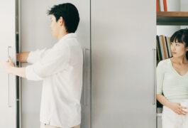 一个男人把手伸进橱柜,一个女人在一旁看着