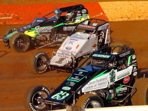 Bryan Clauson (63), Robert Ballou (1) and Chase Stockon go three-wide during AMSOIL USAC National Sprint Car Series competition at Lincoln Speedway in 2016. (Hein Brothers Photo)