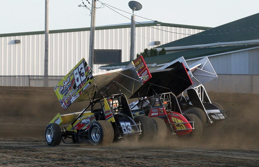 Broc Martin (83), Chris Andrews (25) and Jac Haudenschild go three-wide into turn one during heat race action on Saturday night at Attica Raceway Park. (Todd Ridgeway Photo)