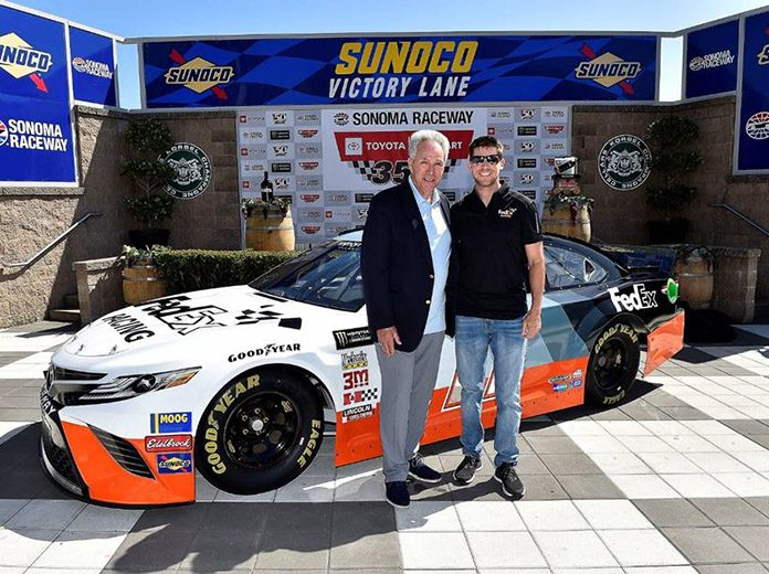 Denny Hamlin (right) and Darrell Waltrip pose in front of the car Hamlin will drive during the Bojangles Southern 500 later this year.