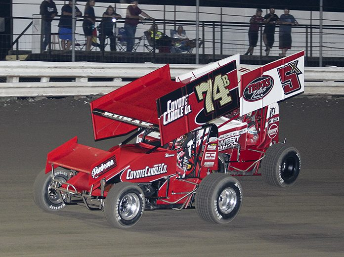 Jake Bubak (74) races by Jason Martin en route to victory Friday at the Belleville High Banks. (Don Holbrook Photo)