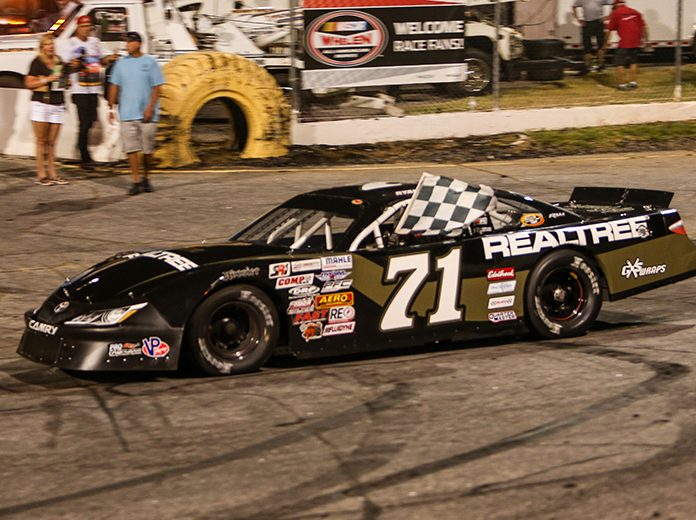 Ryan Repko celebrates with the checkered flag after winning Saturday night at Hickory Motor Speedway. (Adam Fenwick Photo)