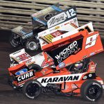 James McFadden (9) races under Brian Brown (21) and Joey Saldana at Knoxville Raceway. (Frank Smith photo)
