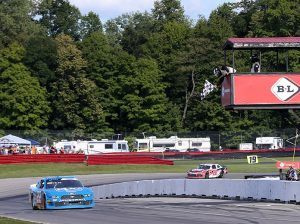 Austin Cindric takes the checkered flag to win the B&L Transport 170 Saturday at the Mid-Ohio Sports Car Course. (HHP/Tim Parks Photo)