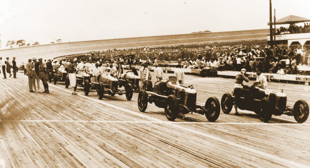 Cars assem- ble on the grid for a 1920's board track race.