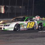 Bryan Kruczek carries the checkered flag following his win in the Oxford Plains 150 on Saturday. (Ken MacIsaac Photo)