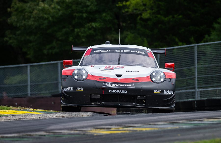 The No. 912 Porsche of Earl Bamber and Laurens Vanthoor hops a curb during Sunday's Michelin GT Challenge at Virginia Int'l Raceway. (Sarah Weeks Photo)