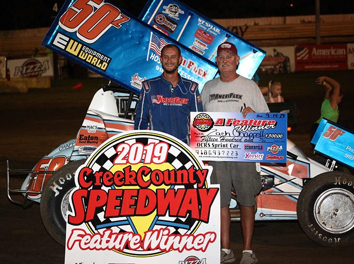 Zach Chappell shares victory lane with his father, David, after winning Saturday night at Creek County Speedway. (Richard Bales Photo)