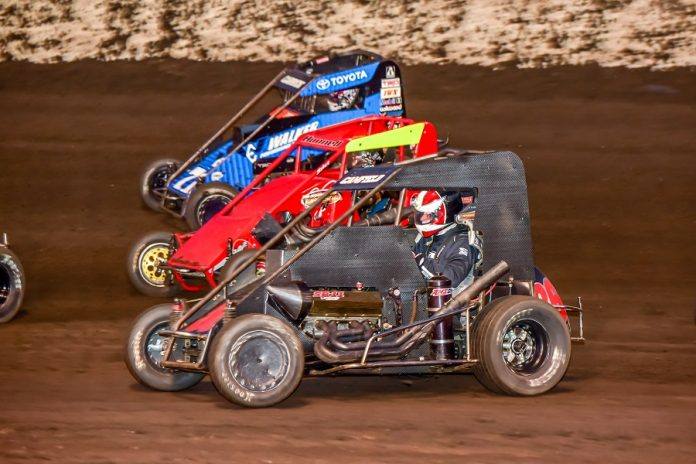 Dalton Camfield (86), Broc Hunnell (103) and Tanner Carrick go three-wide in Saturday's POWRi National Midget League feature at Macon Speedway. (Mark Coffman photo)