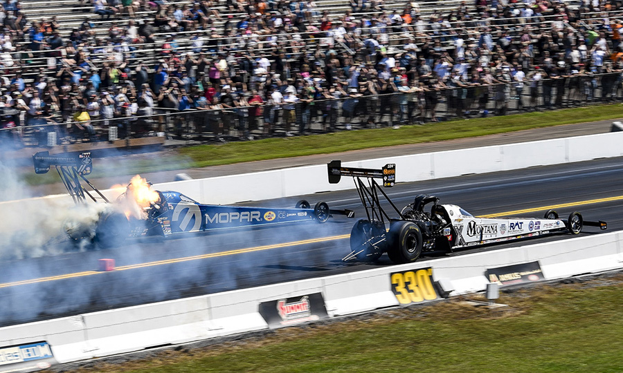 The engine in Leah Pritchett's Top Fuel dragster explodes as Austin Prock drives by during the Mopar Express Lane NHRA Nationals at Maple Grove Raceway. (Dennis Bicksler Photo)