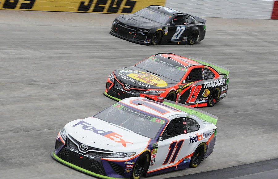 Denny Hamlin (11) and Martin Truex Jr. (19) pass the slower car of Joe Nemechek during Sunday's Drydene 400 at Dover Int'l Speedway. (Dave Moulthrop Photo)