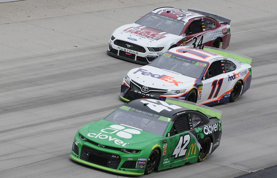 Kyle Larson (42) and Denny Hamlin (11) battle for position as they bypass Michael McDowell during Sunday's Drydene 400 at Dover Int'l Speedway. (Dave Moulthrop Photo)